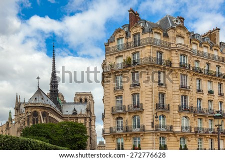 View on typical parisian building as Notre Dame de Paris Cathedral on background. - stock photo