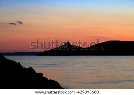 View on water surface and mountain silhouette with lighthouse at pink sunset
