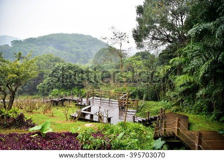 View on wooden walkway in landscaped park - stock photo