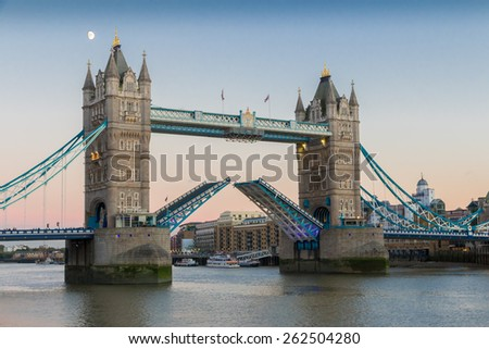 View on world famous London Tower Bridge with the bridge open for ship traffic shortly before sunset on a clear summer evening - stock photo
