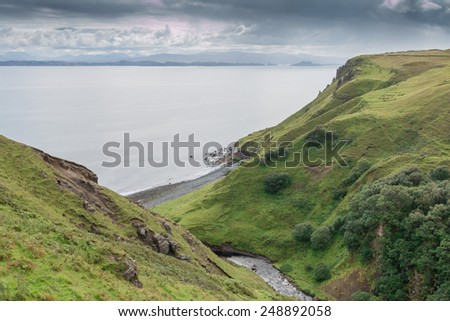 View onto the lush green rock coastline of the Isle of Skye, Scotland - stock photo