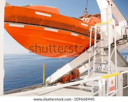 View out to sea of an orange lifeboat on deck of cruise ship suspended from a heavy metal davit - stock photo