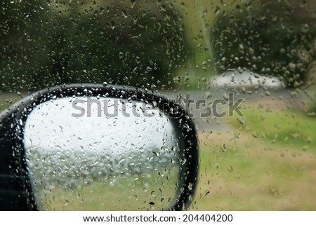 view out wet car windows on a rainy day at the beach