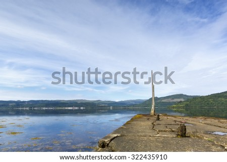 View over a Scottish Loch. Blue skies and water reflections. Taken in summer and demonstrates tranquility. - stock photo