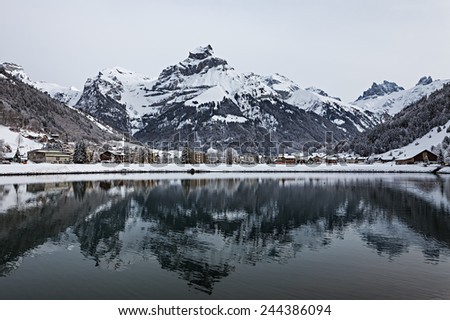 View over a Swiss Village by a lake in the Alps, covered in snow during winter. Engelberg, Switzerland. - stock photo