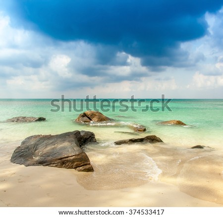 view over a tropical beach with granite rocks, white sand and a turquoise indian ocean under a blue sky