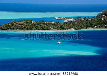 View over beautiful turquoise lagoon of bungalows, island and boats.  Tahiti, Society Islands, French Polynesia. - stock photo