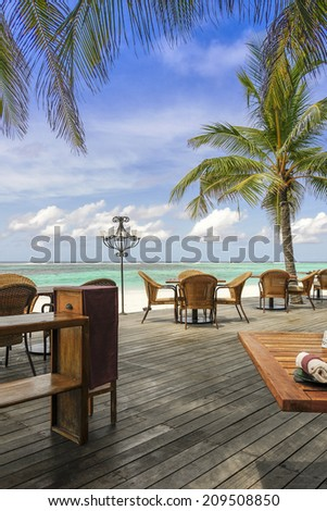 View over chairs and tables of a tropical beach restaurant with palm trees and blue ocean - stock photo