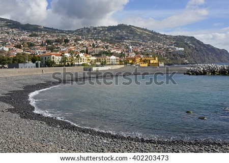 View over city and surrounding hills from the seafront promenade in Funchal, Madeira, Portugal. With unrecognizable people in background
