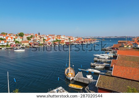 View over Fiskebackskil an old coast village on the Swedish west coast, with Lysekil city in the background at summer - stock photo