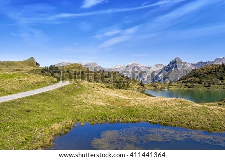 View over mountain lake landscape with peaks in the distance, green grass hills and blue sky, Switzerland, Truebsee near Engelberg - stock photo