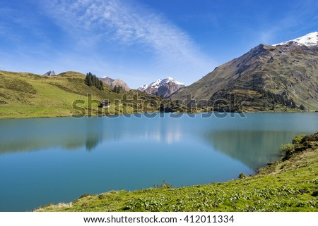 View over mountain lake landscape with peaks in the distance, green grass hills, blue sky, Switzerland, Truebsee near Engelberg - stock photo