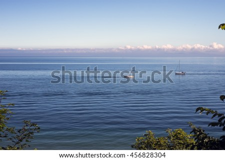 View over Oeresund with two sailboats -  Dronningmoelle, Denmark - stock photo