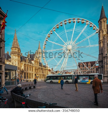 View over plaza in Ghent, Belgium,  with a traditional Christmas wheel and a film emulation cyan sky and warmer tones and colors. Available in high resolution panorama square format for large prints - stock photo