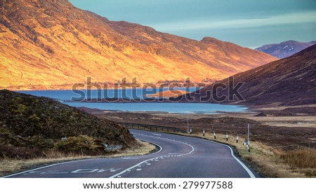 View over Scotland mountains with a road in the sunset light - stock photo