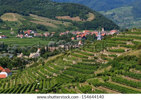 View over terraced vineyards to Duernstein, a picturesque town on the Danube river. Duernstein is a famous tourist attraction and one of the wine centers in the Wachau. - stock photo