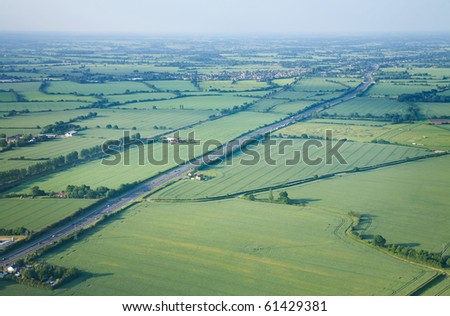 view over the early summer green fields and a dual carriageway road from the air; East Anglia; UK - stock photo