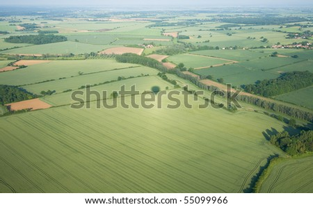 view over the early summer green fields from hot air balloon; East Anglia; UK - stock photo