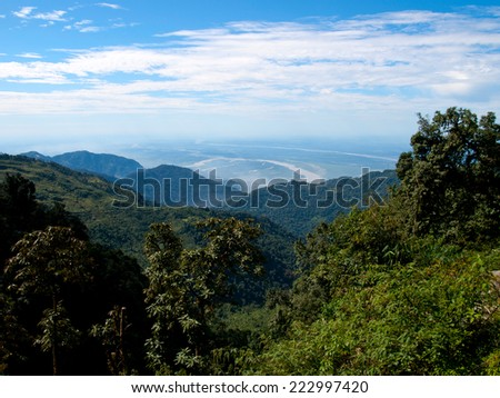 View over the lower section of the Himalayan mountains in India as seen from Bhutan with the lush green forests in front - stock photo