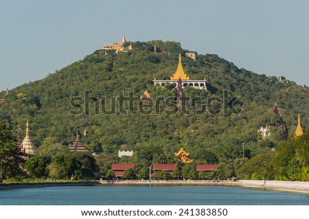 View over the moat of Mandalay Palace to Mandalay Hill with its many temples - stock photo