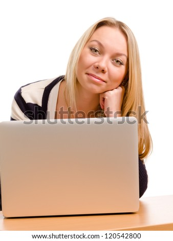 View over the raised screen of a laptop of a smiling woman leaning her head on her fist looking at the camera - stock photo