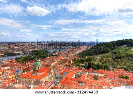 view over the roofs of Prague in the Czech Republic with a brightly shining blue sky and snow-white clouds - stock photo