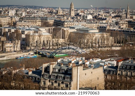 View over the rooftops of Paris, France with its streets of historical buildings to a distant skyline under a blue sky, travel concept