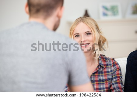View over the shoulder of a colleague of a beautiful smiling young woman in a business meeting - stock photo