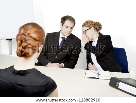 View over the shoulder of a redhead female applicant of two personnel managers conducting a job interview whispering amongst themselves about their impression and decision - stock photo