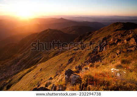 View past Mansfield at sunset from the summit of Mt Buller in Victoria, Australia - stock photo