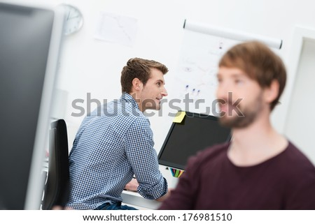 View past the face of a colleague to a handsome young businessman sitting at his desk at work in the office - stock photo