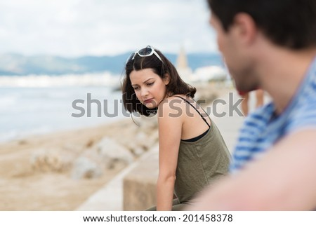 View past the shoulder of a man watching a beautiful young woman daydreaming at the beach sitting on a wall overlooking the ocean staring pensively at the ground - stock photo