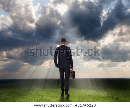 View rear of businessman on dramatic cloud scene background