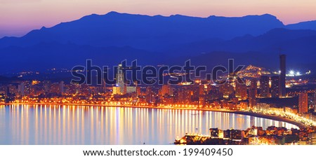 View the night city with lights reflected in sea at sunset (View Benidorm, Spain) - stock photo