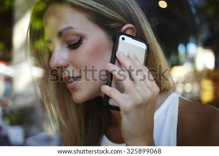 View though the window of a attractive woman calling with her cell telephone while sitting on coffee shop during breakfast, gorgeous female having smart phone conversation with her good friend - stock photo