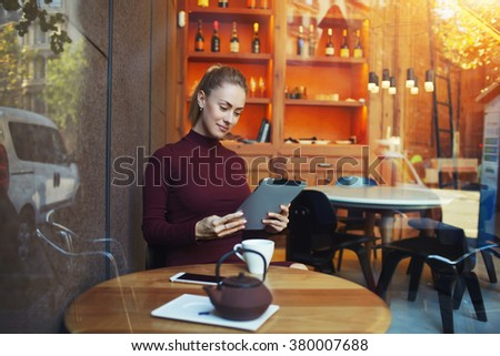 View though the window of a woman reading electronic book on digital tablet during lunch break in comfortable cafe inside, pretty female work on touch pad while sitting in modern restaurant interior  - stock photo