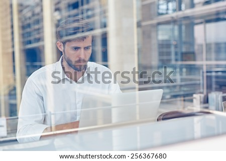 View through a window of a corporate executive working on his laptop - stock photo