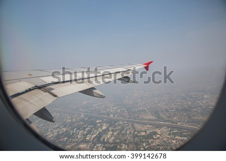 View through a window of an airplane wing aircraft flying above land and blue sky. - stock photo