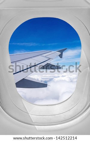 View through airplane window, wing over the clouds - stock photo