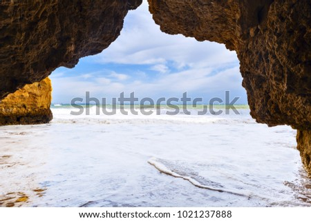 View through an arch of rocky cliff at  Praia Dona Ana near Lagos city, Portugal.