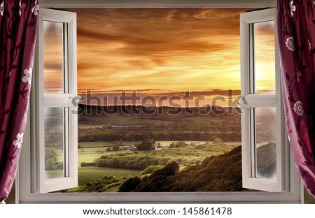 View through an open window onto rural landscape and sunset - stock photo