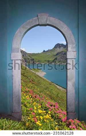 view through arched door; artificial lake, alpine flowers and mountains  - stock photo