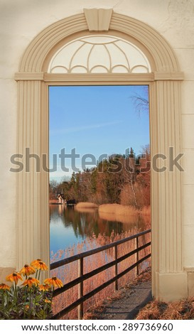 view through arched door, autumnal lakeside path - stock photo