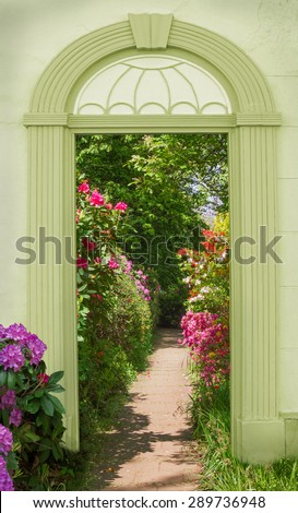 view through arched door, colorful blooming rhododendrons - stock photo