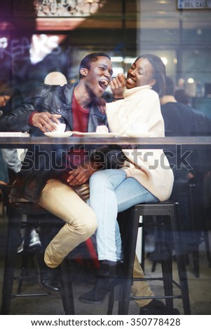 View through cafe window of a young happy dark skinned man and woman having fun while sitting together in bar, cheerful smiling black couple enjoying recreation time while having lunch in coffee shop - stock photo