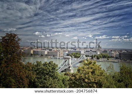 View through green trees  of the Danube river and city landmarks as Chain bridge and Parliament in Budapest in Hungary under a cloudy sky in a sunny summer day - stock photo