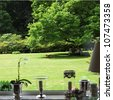 View through living room window View through living room window of a lush green secluded garden with shade trees and a neatly manicured lawn - stock photo