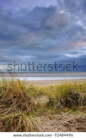 View through long maram grass sand dunes out to sea at sunset - stock photo