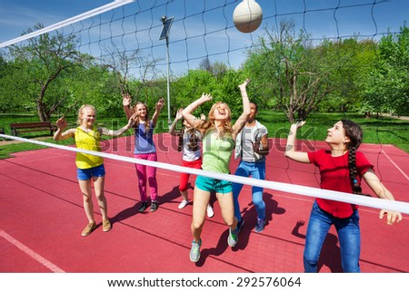 View through net on game of girls playing together - stock photo