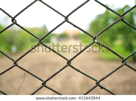 View through steel wire fence. Tiny garden in a Romanian village